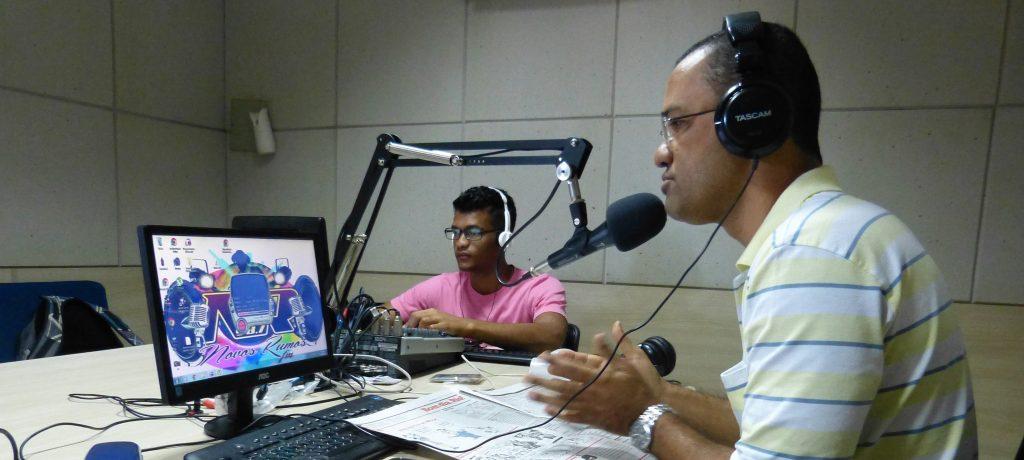 Ein Mann sitzt an einem Tisch und spricht in ein Mikrofon. Vor ihm stehen ein Computerbildschirm und eine Tastatur