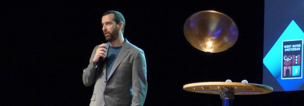 Ein Mann mit kurzen schwarzen Haaren und grauem Anzug steht auf einer Bühne und spricht in ein Mikro